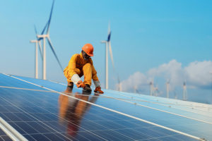 energy sector worked on solar panels with wind turbines in back